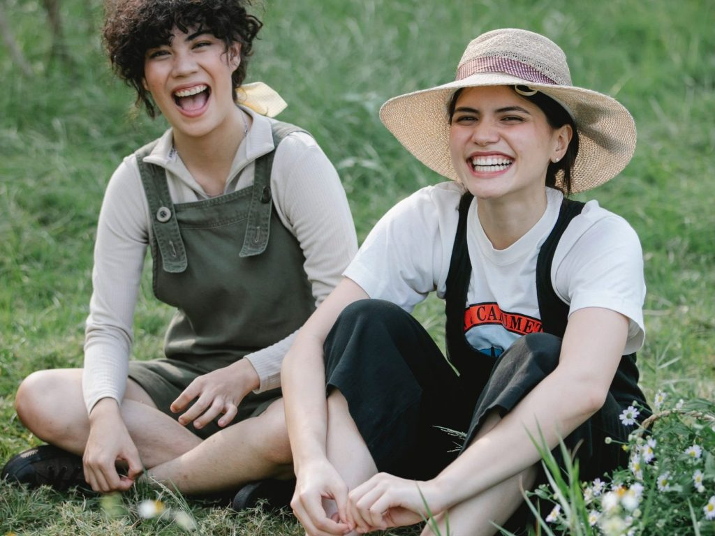 Two people smiling at the camera. They are wearing dungarees and sitting on grass