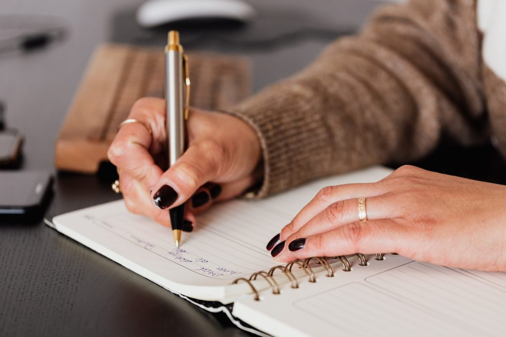 An image of hands writing in a notepad. The person has painted nails and is wearing gold rings.